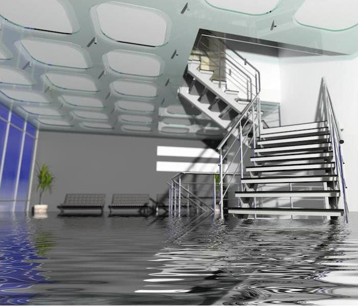 Flooding in large room with staircase partially submerged in water.